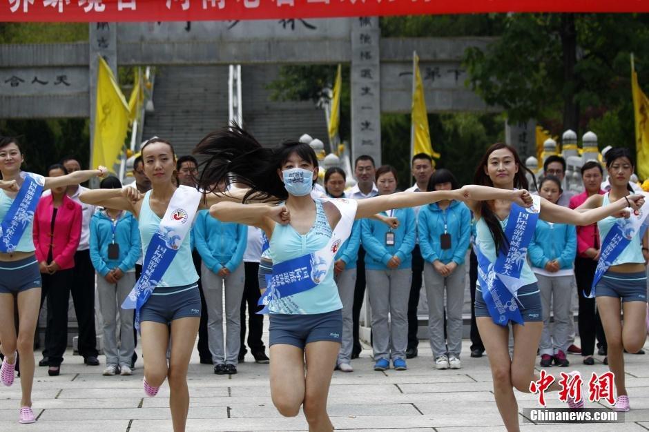 """6月5日世界环境日,国际旅游海峡两岸形象大使大赛的参赛选手们在河南老君山广场戴口罩进行舞蹈""""快闪"""",呼吁保护环境拒绝污染。中新社发 王中举 摄"""