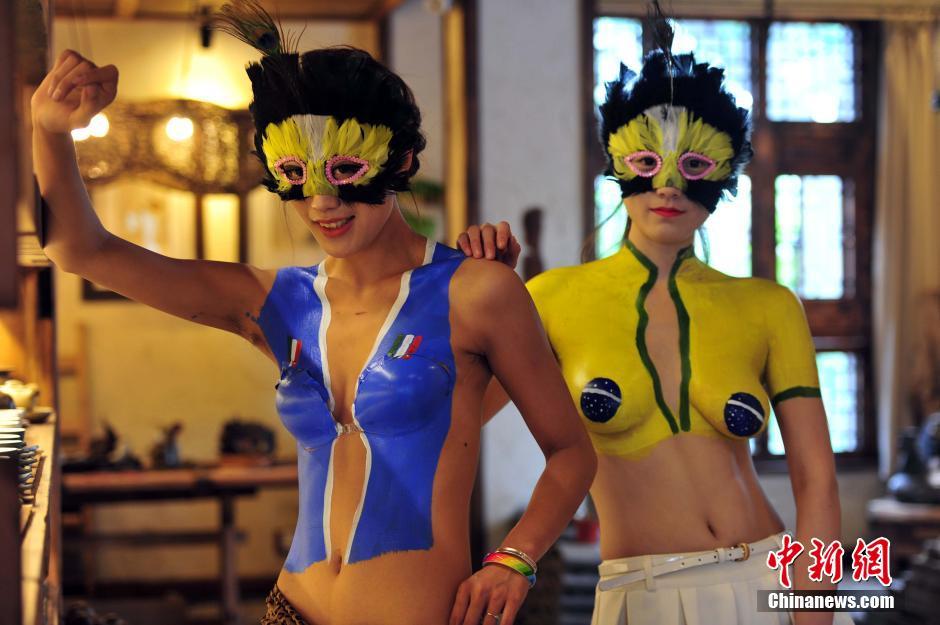 6月13日,身上绘有巴西和意大利足球队服色彩的模特在沈阳亮相。
