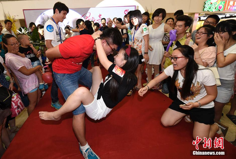"""单腿独立式、骑跨式、肩背式……8月2日晚,一场火热的接吻大赛在南京八佰伴举行,参赛情侣们通过多轮姿势""""技巧""""的比拼争夺钻戒大奖,同时也用KISS的方式大胆表达对爱人的真挚情义。寒单 摄"""