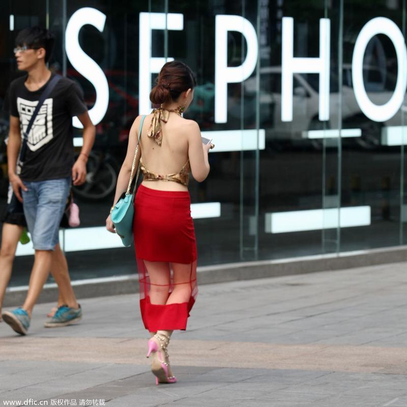 """2014年8月2日,重庆,美女穿着清凉装行走在山城街头,引众多市民关注。某美女上半身身着""""肚兜"""",下半身则是透视长裙,脚踩铆钉鞋,受到街上众多""""注目礼""""。"""