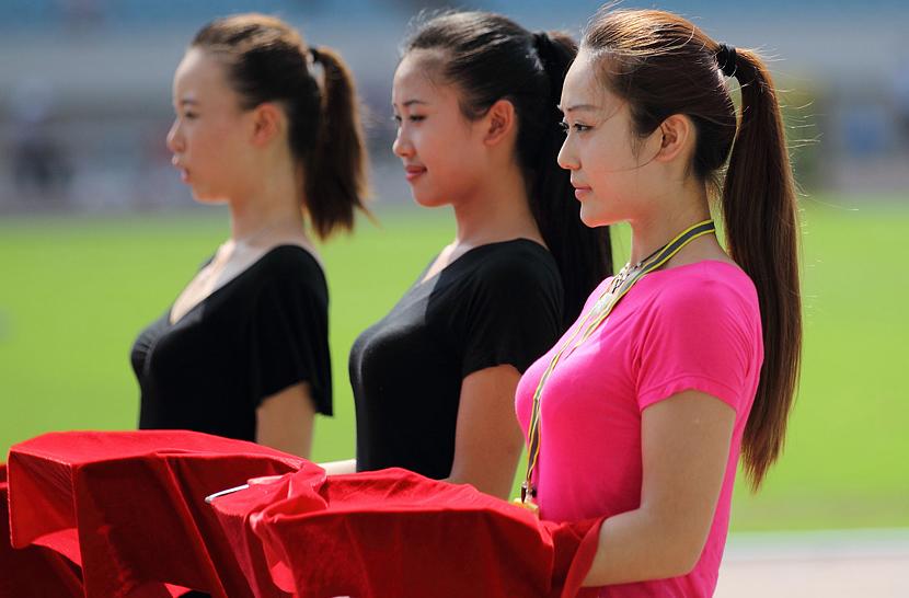 7月17日,亚青会颁奖礼仪小姐在南京奥体中心体育场举行的田径测试赛上演练颁奖全过程。2013亚洲青年运动会将在8月16日开幕。中新社发 泱波 摄