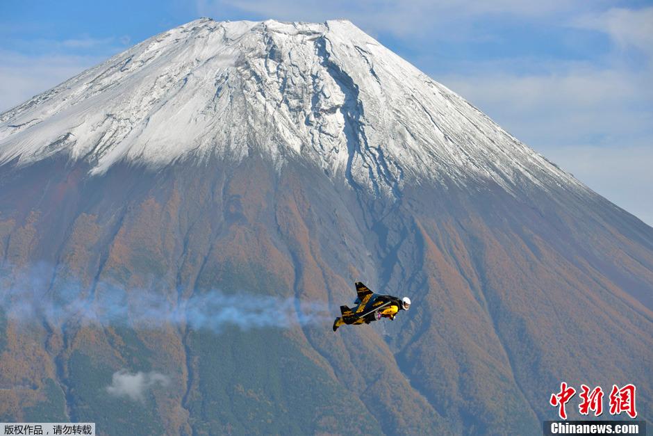 """据外电11月1日发布的图片显示,瑞士""""喷气""""飞人伊夫・罗希在日本富士山前飞过。自10月28日到11月3日,他已""""飞""""过富士山达9次。"""