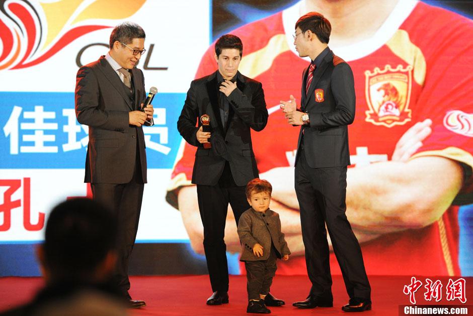 11月24日,2012-2013赛季中超联赛颁奖典礼在北京举行。即将离开广州恒大的孔卡终于如愿以偿得到中超MVP奖项。孔卡抱着儿子本杰明上台领奖,孔卡儿子也因此成为颁奖礼最抢镜的明星。中新网记者 张龙云 摄