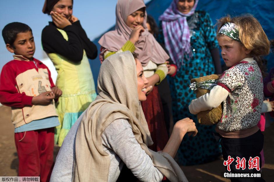 朱莉访问叙利亚难民营附近的城市,穿着当地服装与那里的孩子亲切交流。