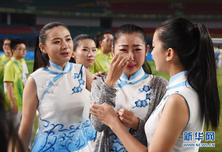 8月27日,礼仪志愿者安慰哭泣的同伴。当日,2014南京青奥会结束全部比赛,足球赛场专门为服务赛事的志愿者举行了告别晚会。 新华社记者 姜克红 摄