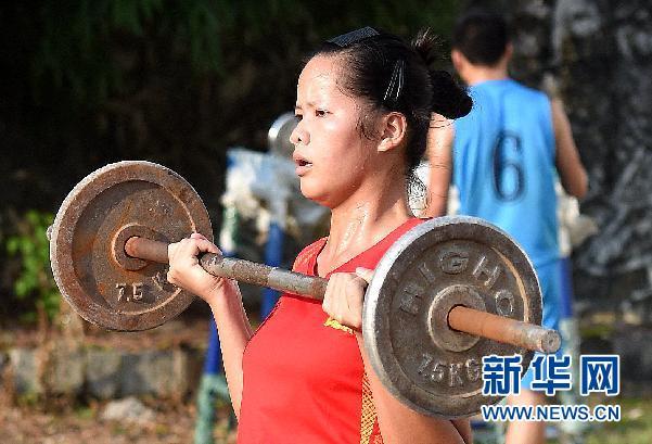 9月12日,大化县第二中学的女生利用杠铃练习手臂力量。
