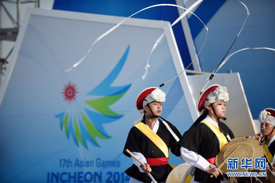 """9月19日,演员在开幕式主场馆的广场舞台上表演韩国传统舞蹈""""象帽舞"""",为即将开幕的亚运会助兴。"""