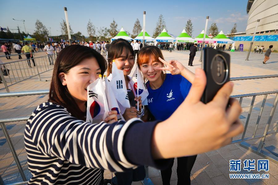 9月19日,观众与志愿者在韩国仁川亚运会主体育场外自拍合影,等待亚运会的开幕。