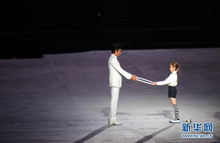 9月19日,第17届亚洲运动会开幕式在仁川亚运会主体育场举行。 这是韩国演员张东健(左)与小女孩在表演。 新华社记者孟永民摄