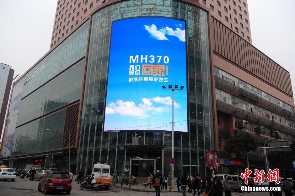 """3月18日,湖北武汉武昌一商业楼的巨大电子屏打出""""MH370,我们等你回家!相信会有奇迹发生""""的字样,为失联同胞祈福。中新社发 张畅 摄"""