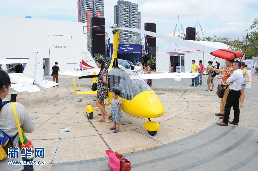 """3月27日,参观者在展出的小型直升机前留影。当日,2014海天盛筵""""中国游艇、公务机及尊贵生活方式展""""在海南三亚开幕。 新华社发(夏一方 摄)"""