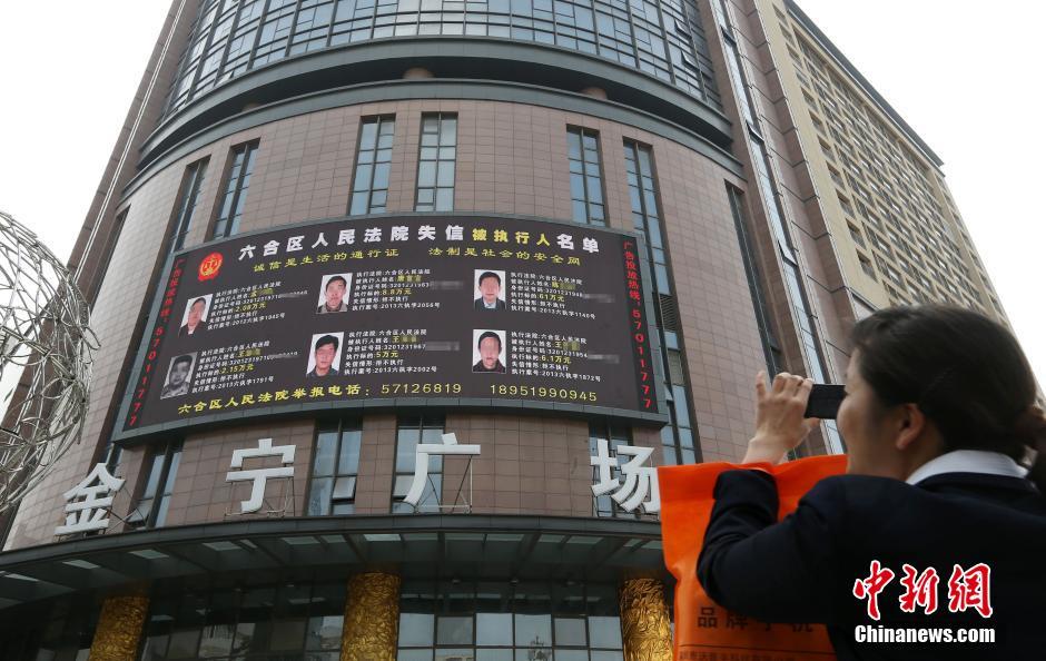 """4月14日,街头的大屏幕滚动播放着""""老赖""""相关信息。"""