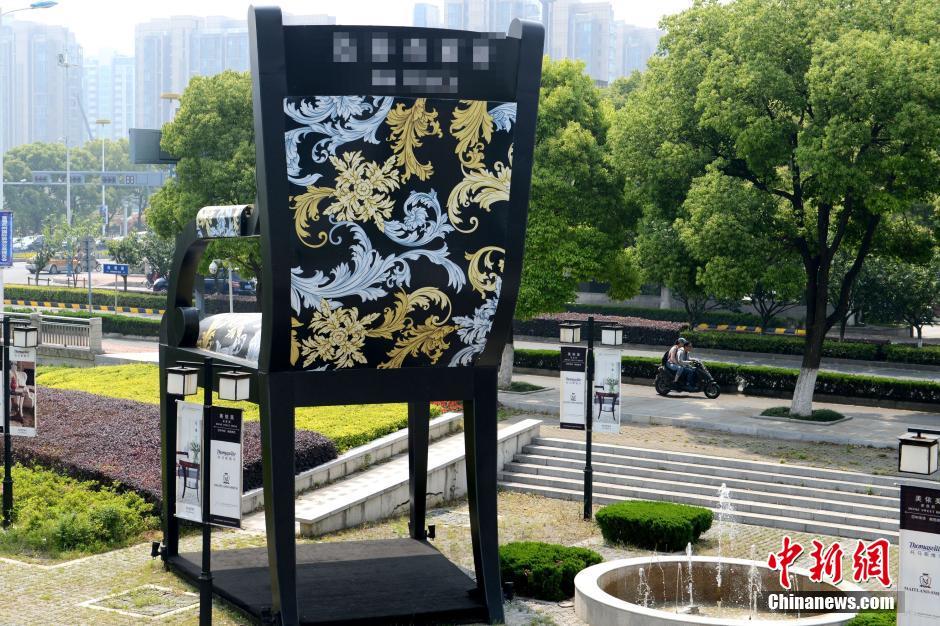 """5月8日,一把高约10米的巨型椅子出现在江苏苏州街头,""""巨无霸""""式的身材吸引了过往路人好奇的目光。中新社发 王思哲 摄"""