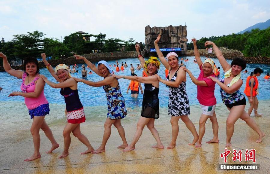6月29日,夏日炎炎,一群中国大妈在广东森波拉冰川水谷的游泳池边大跳广场舞,吸引了众多游客的眼光。中新社发 梁永强 摄