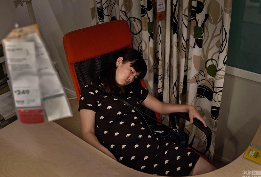图为顾客在家具商场陈列的沙发或床上睡觉休息。