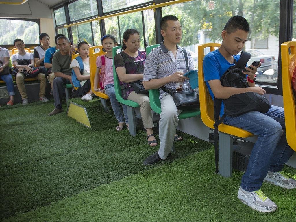 """2014年7月16日,新疆维吾尔自治区乌鲁木齐市天山区东泉路,931路公交车司机外力・吐尔迪开着铺满""""草坪""""的公交车,为乘坐公交车的市民们带来别样的感受。"""