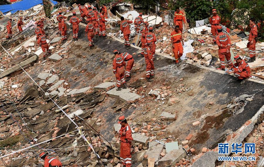 8月8日,救援人员在云南鲁甸县龙头山镇被震毁的废墟上搜寻失踪者。