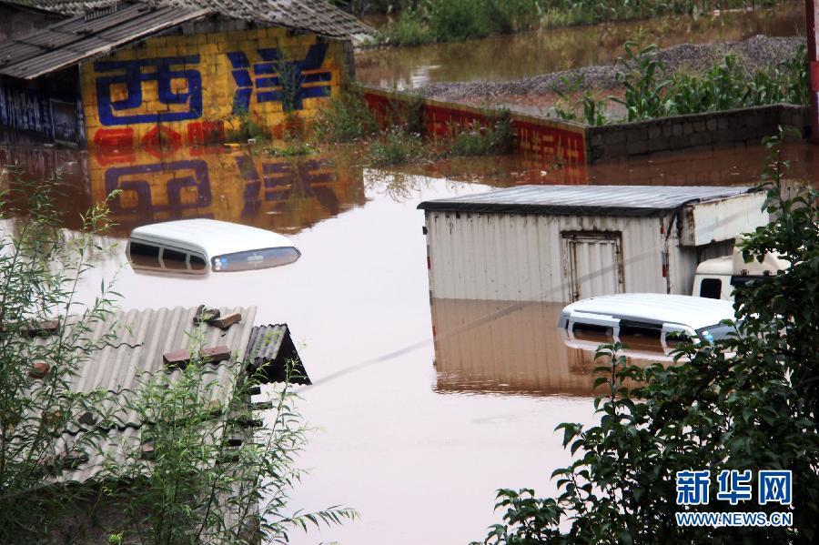 8月12日在贵州威宁县猴场镇街上村拍摄的被洪水淹没的车辆和房屋。