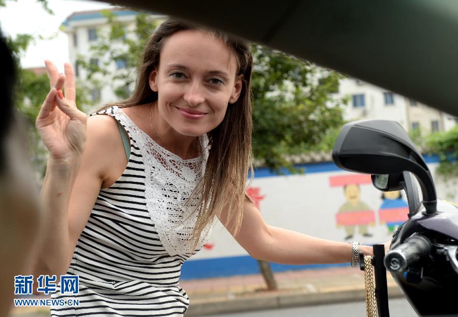 9月1日,安娜骑着电动车与小区的一位车主打招呼。