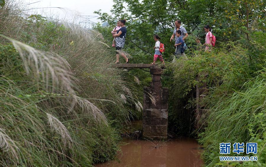 9月9日,陈红权、明红艳护送孩子们放学回家。