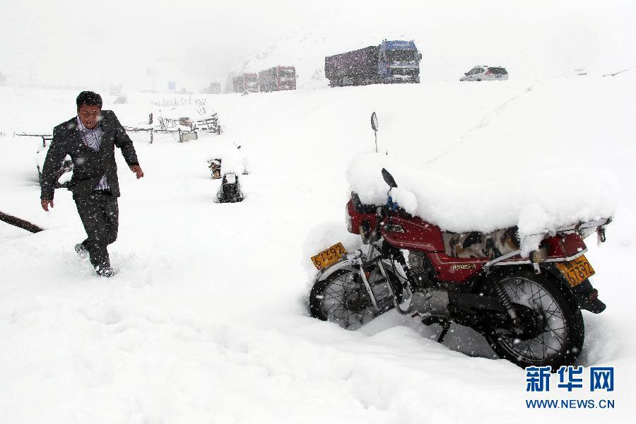 9月12日,车辆在新疆哈密降雪路段缓慢行驶。受冷空气影响,新疆哈密地区当日降下了金秋首场大雪,给当地农牧业和交通带来了不同程度的影响。 新华社发(普拉提 摄)