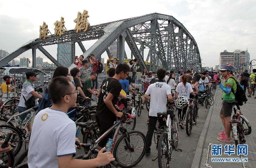 """9月21日,广州单车爱好者推着自行车行经海珠桥。当日,广东广州单车爱好者在微信上发起一场快闪活动,以集体有序地推自行车行经海珠桥的方式,支持""""世界无车日""""。"""