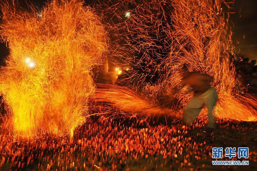 """10月2日,一名大汉光膀赤脚在浙江省磐安县双峰乡东坑村表演""""炼火""""。"""