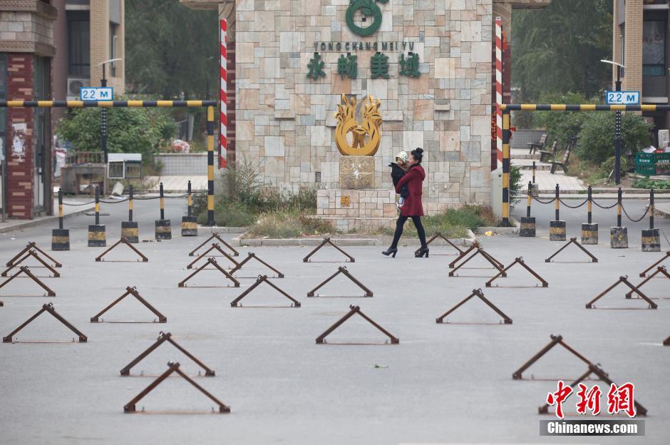 10月9日,市民从长春一布满车位地锁的小区门前走过。
