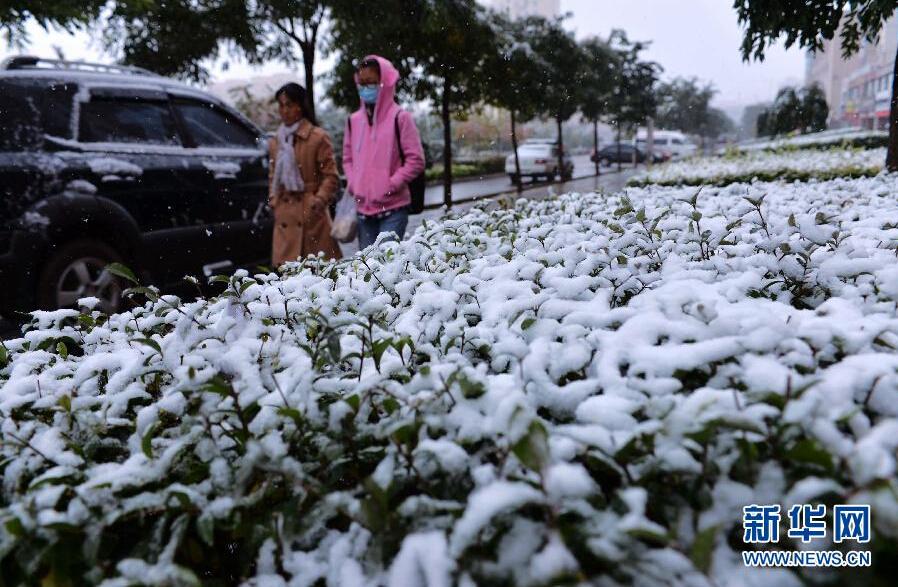 10月11日,两名行人冒雪走在甘肃省渭源县街头。当日,受新疆东移较强冷空气影响,甘肃省内多地出现今秋以来首场降雪天气,气温普遍下降8摄氏度以上。 新华社记者 陈斌 摄