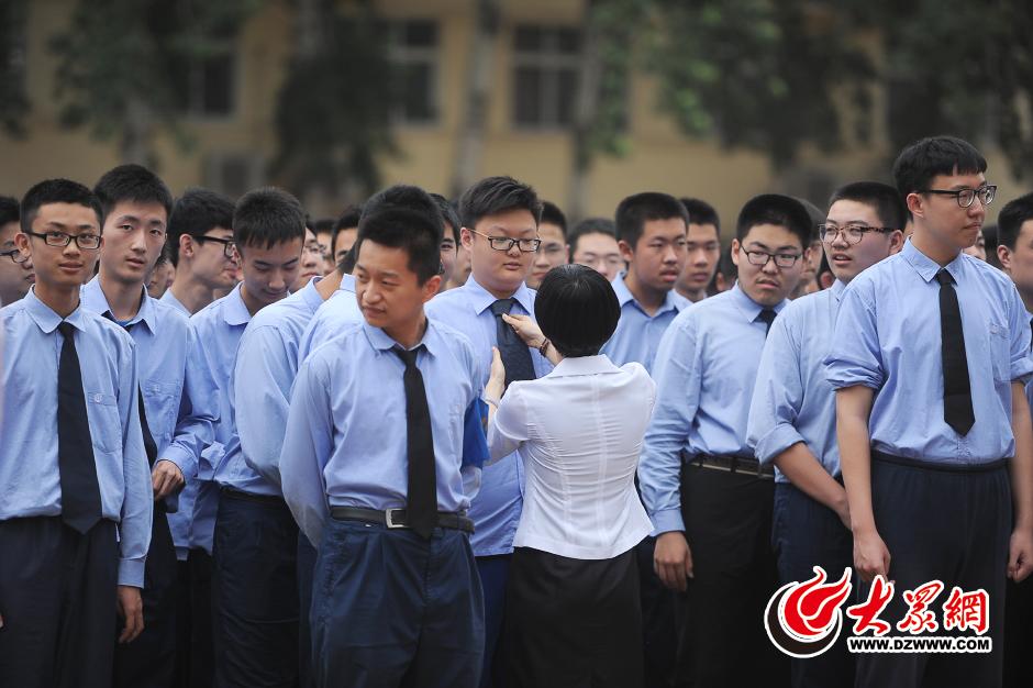 4日,在山东省实验中学体育场,一名老师给学生整理校服.当日,