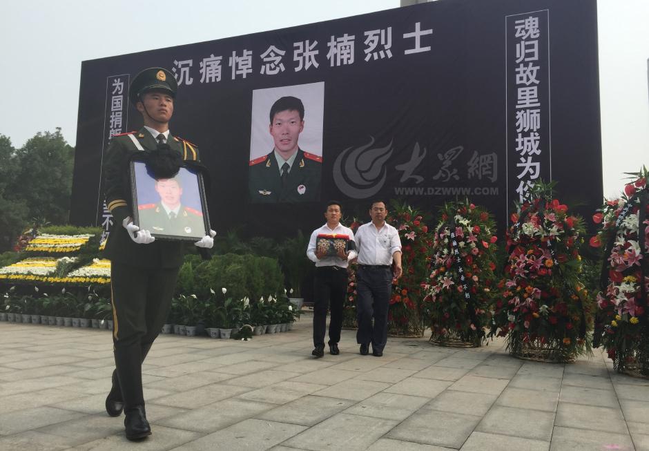 8月2日下午,在河北沧州烈士陵园,一名武警战士手捧遗像,张楠烈士堂弟张希怀抱骨灰盒,由四名礼兵引领护送,礼步行进到烈士安葬地。大众网记者 王长坤 摄