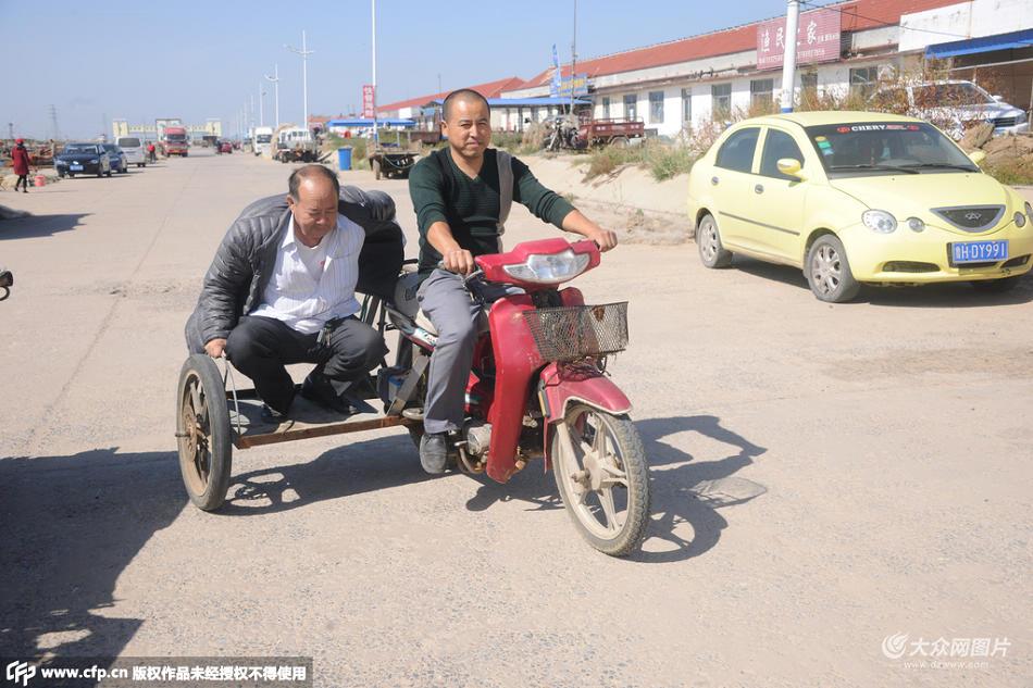 2015年10月3日,山东市东营垦利县红光渔港,一名男子将自己的摩托车改装成三轮摩托车载客,吸引众多路人的眼球。