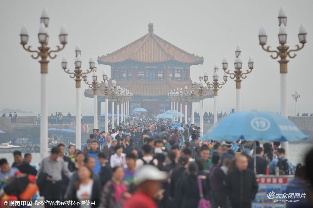 2015年10月15日,山东青岛,栈桥陷入雾霾之中,游客来到海边欣赏海景。