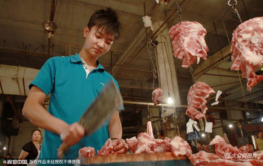 """2012年5月6日,重庆人和农贸市场,卖肉商贩长相酷似明星贾乃亮,阳光、帅气,为人热情,切猪肉刀法精准,人称""""猪肉王子""""。"""