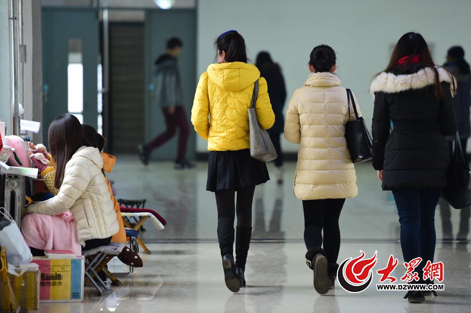 11月30日,山东师范大学长清湖校区,在教学楼的走廊里,几名考研学生面对暖气片背诵复习资料。大众网记者 王长坤 摄