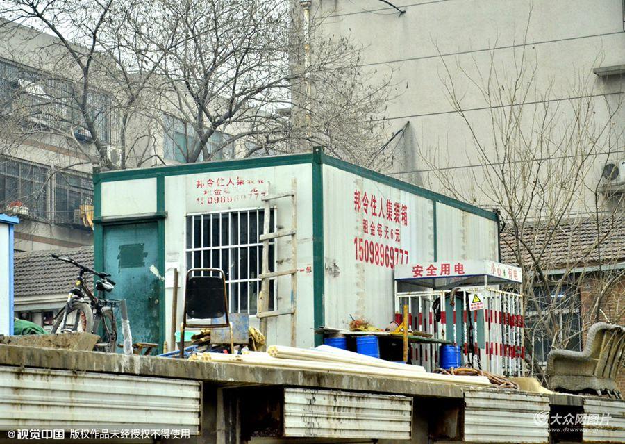 """2015年12月22日,济南,街头一""""房屋""""看上去外观像板房,形状像货柜,外墙上""""住人集装箱租金每天6元""""的广告引人注目。"""