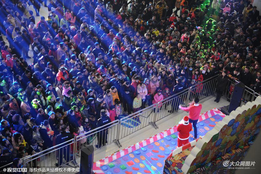 """2015年12月24日,济南泉城路上,近千名市民聚集在一起看节目苦等圣诞老人""""抽奖""""。"""