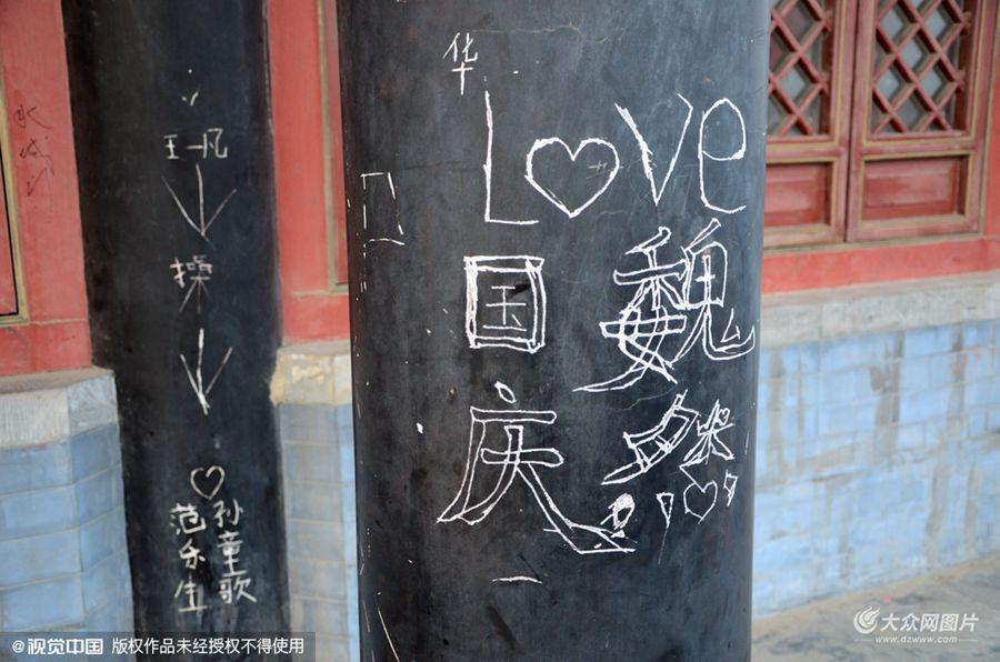 """2016年2月25日,山东聊城市,一旅游景点城楼柱上被涂刻满了各种""""秀恩爱""""的字,32根城门柱全部遭涂刻无一幸免。"""
