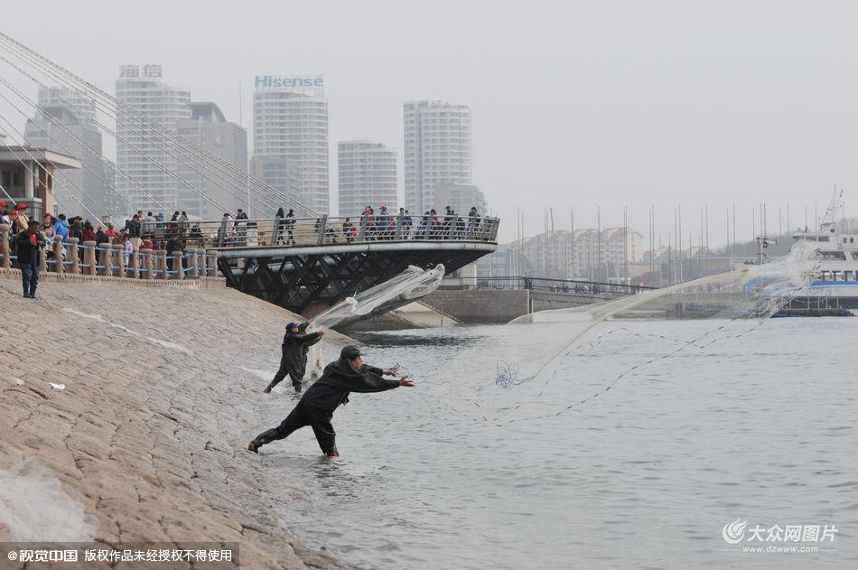 """3月6日,""""禁捕令""""发布第二天,仍有部分市民在青岛市五四广场沿海一带撒网捕鱼,适逢周日,引众多游客围观。"""