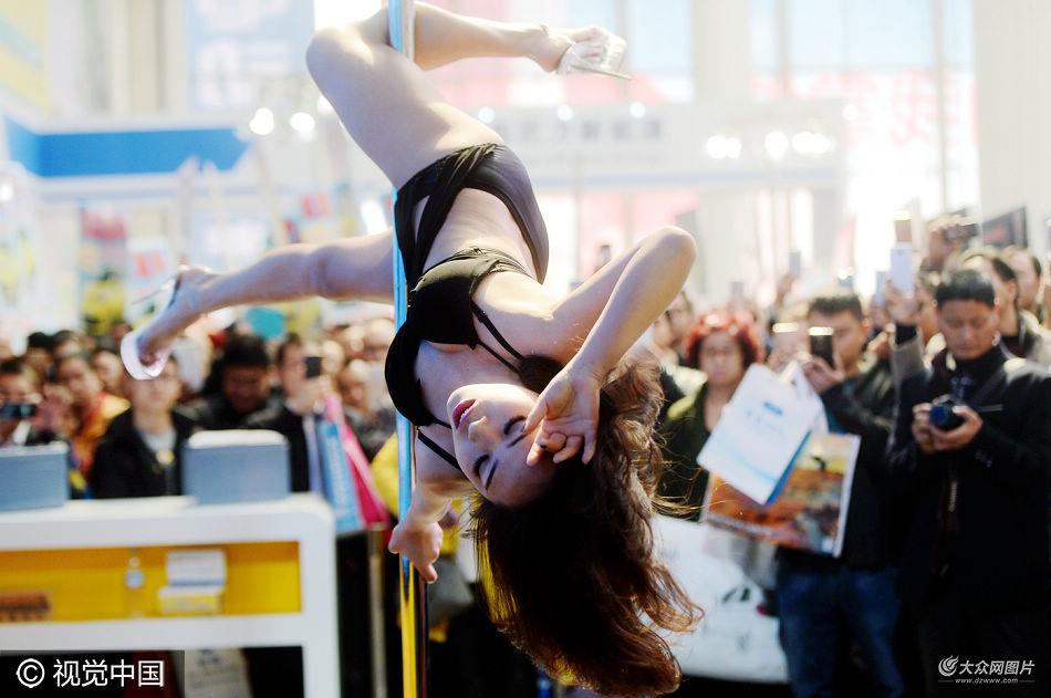 3月11日,一家电池生产厂商参加电动汽车展,邀请女孩身穿连体泳装跳起钢管舞,展示秀美长腿和性感身姿,现场吸引众多男性观众围观拍摄。