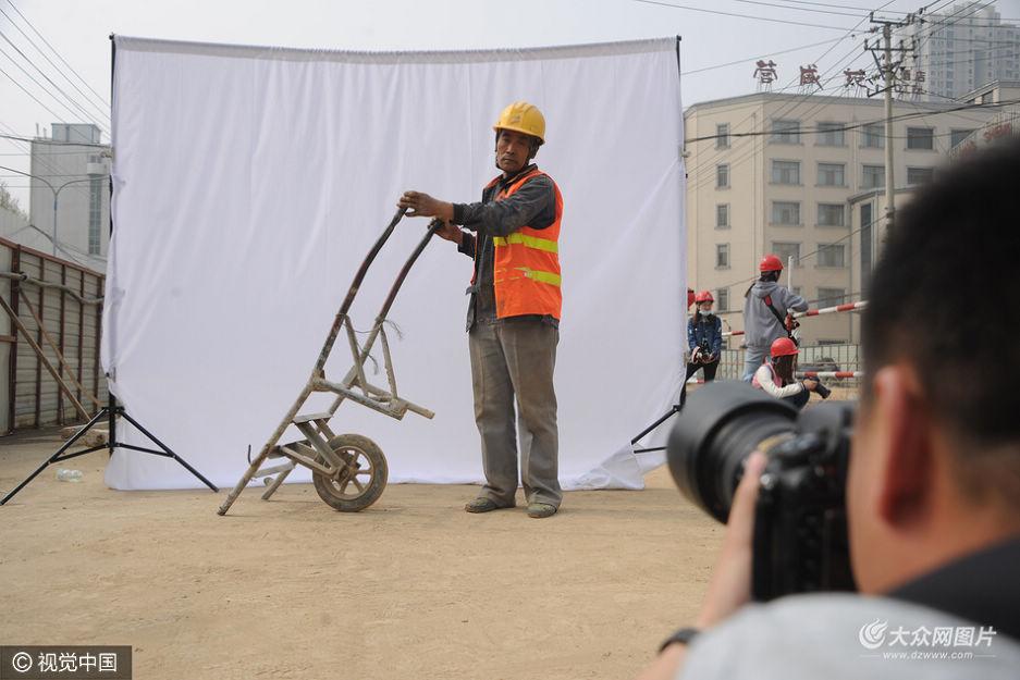 4月7日,济南一工地上,20余名来自山东师范大学摄影系的大学生来工地免费为农名工拍照,并帮他们寄给亲人,为农民工送去了关爱。
