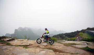 河南8岁男孩悬崖边骑摩托秀车技.jpg
