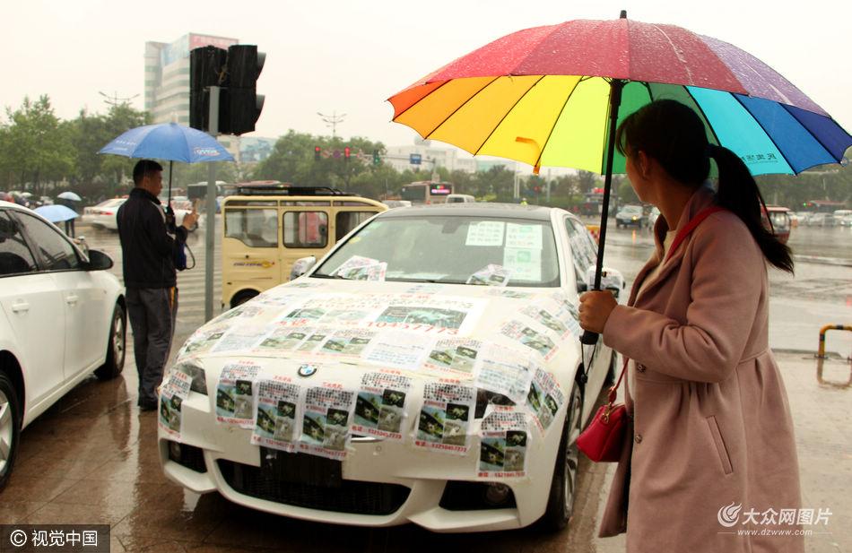 2016年5月9日,聊城迎来降雨,停在城区中心路口停车场的一辆宝马车特别显眼,全车上下贴满寻狗启示。