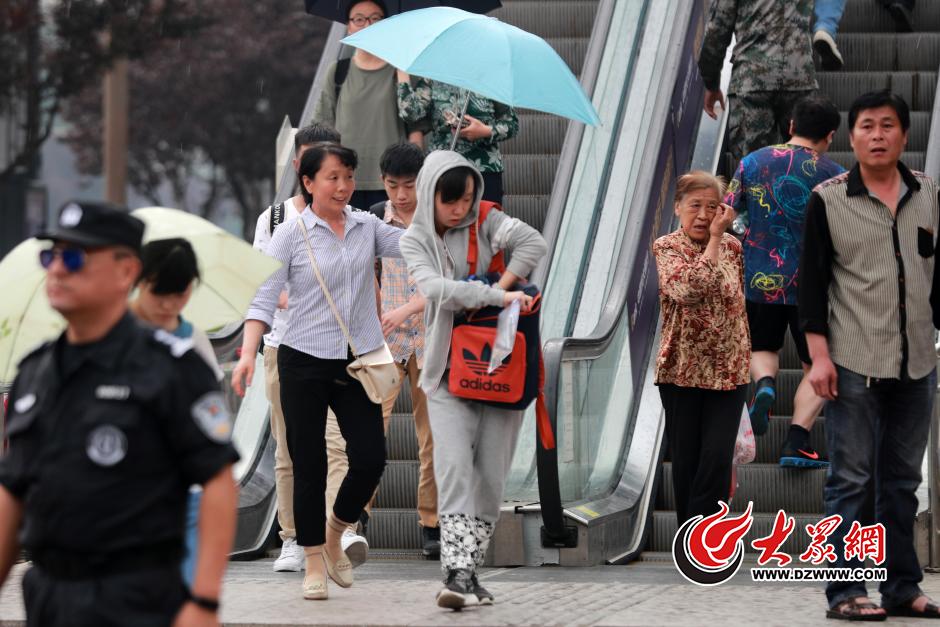 6月7日下午,高考第一天,济南下起了小雨,在山东省实验中学考点外,一家长打着伞送考。大众网记者 王长坤 摄
