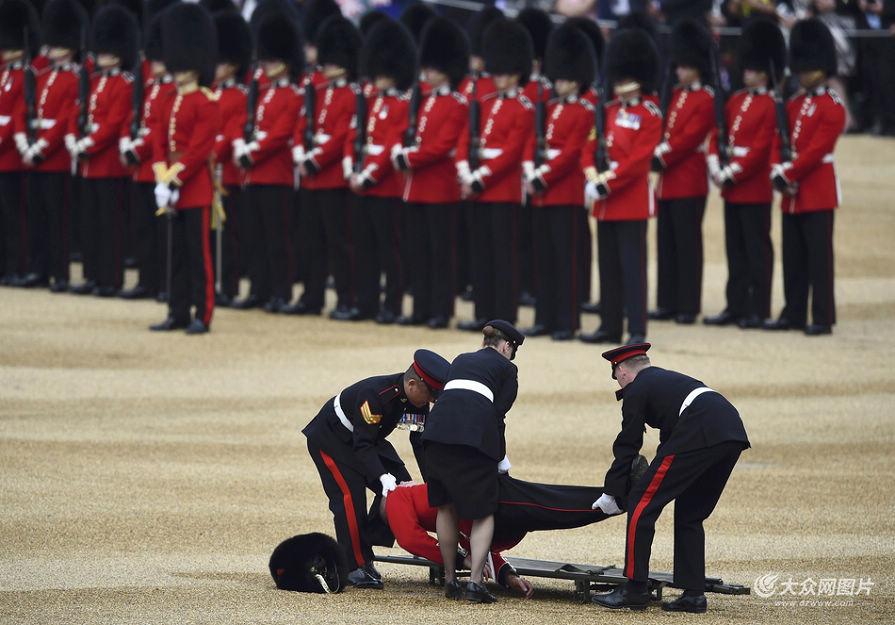 当地时间2016年6月11日,英国伦敦,英国举行皇家军队阅兵仪式纪念女王90岁生日,一名士兵晕倒。