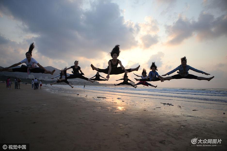 9月23日,青岛石老人海水浴场秋分后迎来美丽海景,游客海边做出高难集体一字马。