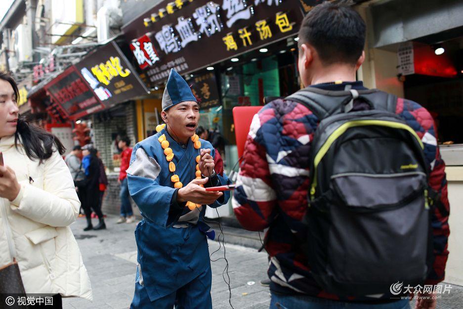 """11月9日下午,网络当红搞怪主播""""YY大傻""""在济南芙蓉街对着一台笔记本电脑欢快歌唱。"""