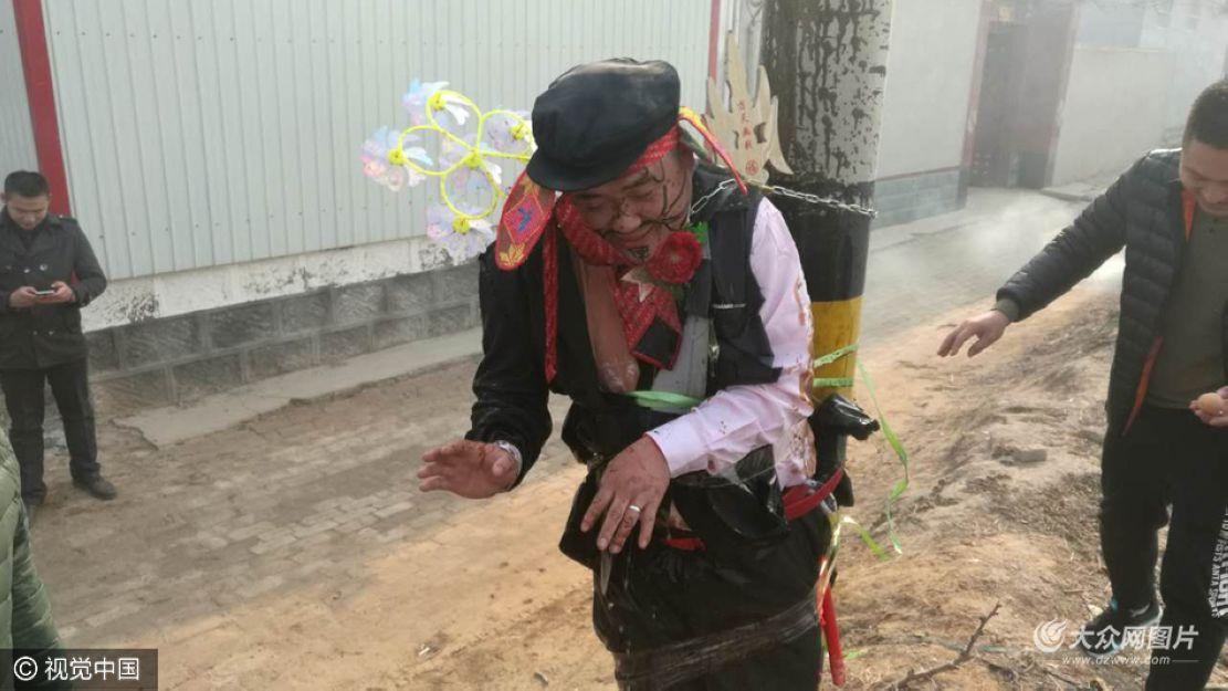 """12月11日,山东滨州,沾化区下洼镇一小伙结婚被穿""""八戒装""""游街,五花大绑在电线杆上,全身泼脏水,头戴小花。"""