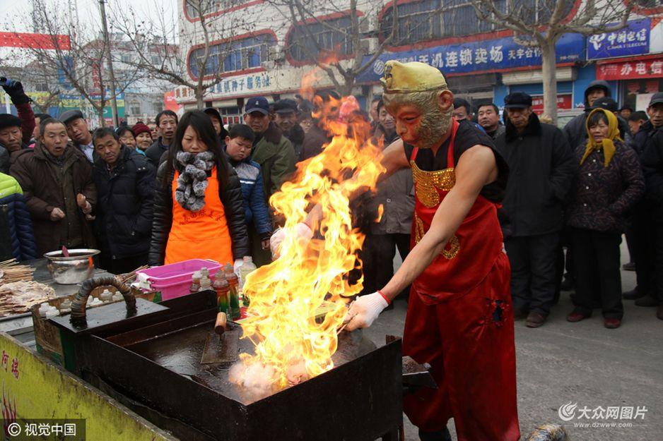 """2月8日,山东滨州,""""大师兄""""光着膀子在零摄氏度的低温中烤鱿鱼。"""