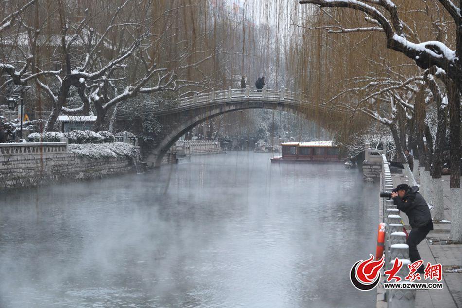"""2月22日早上7点,山东济南,一场降雪过后,护城河黑虎泉段水面上水汽袅袅,烟雾笼罩,呈现""""云雾润蒸""""的景象,构成了一幅奇妙的图画,吸引了不少游人前来观赏拍照。大众网记者 王长坤 摄"""
